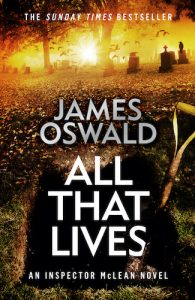 Cover image for All That Lives, book twelve in the Inspector McLean series by James Oswald. Cover shows an open grave, spade handle poking out of it, orange dawn light filtering in through trees and past headstones in the background