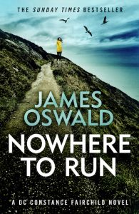 Cover image for Nowhere To Run, book three in the Constance Fairchild series by James Oswald. Image shows a lone woman on a clifftop path, looking back. Beyond her the sea, sky and menacing birds.